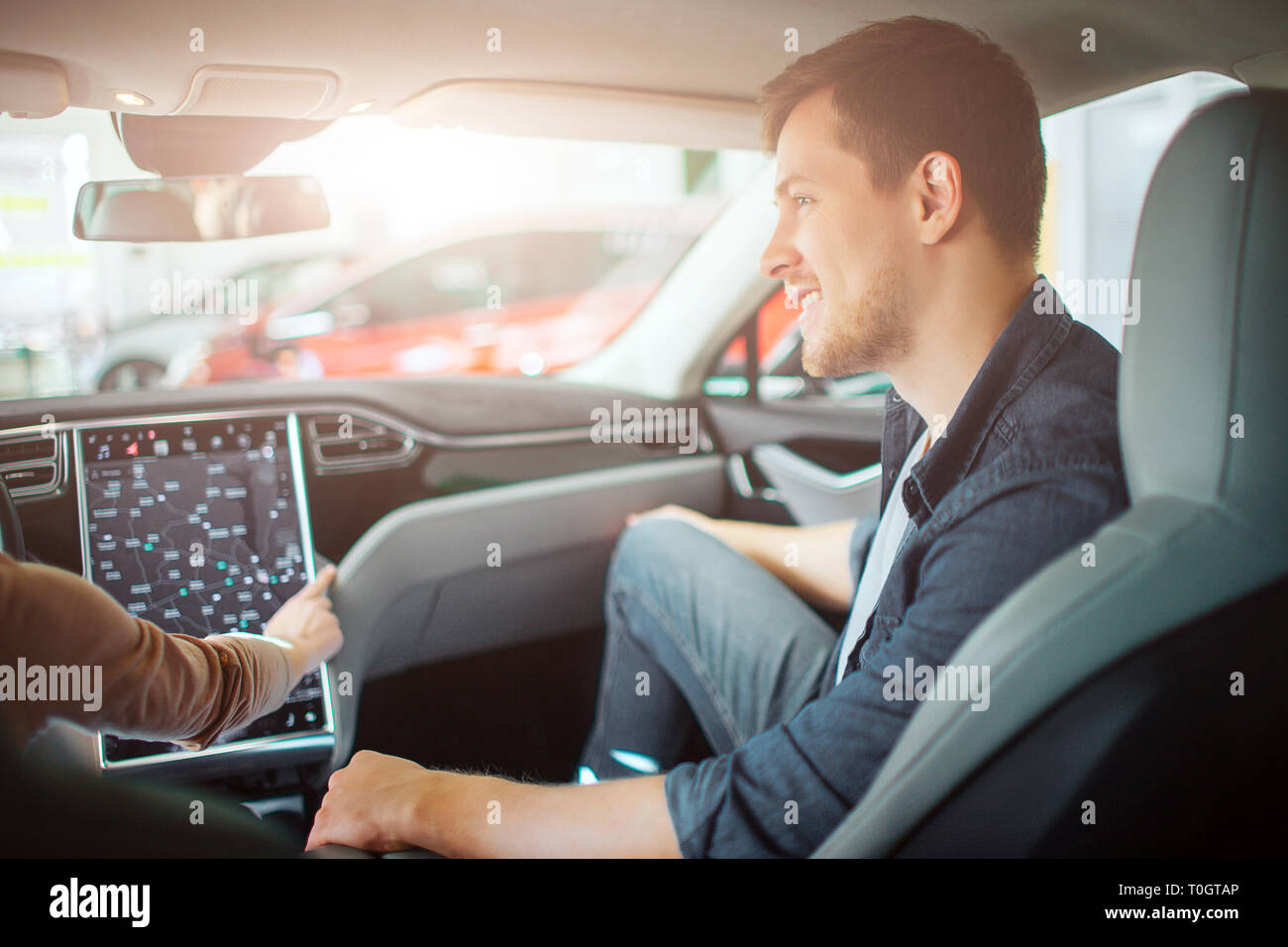 Young couple buying first electric car in the showroom. Attractive glad man looking at his girlfriend while she chooising a way on electronic - Stock Image