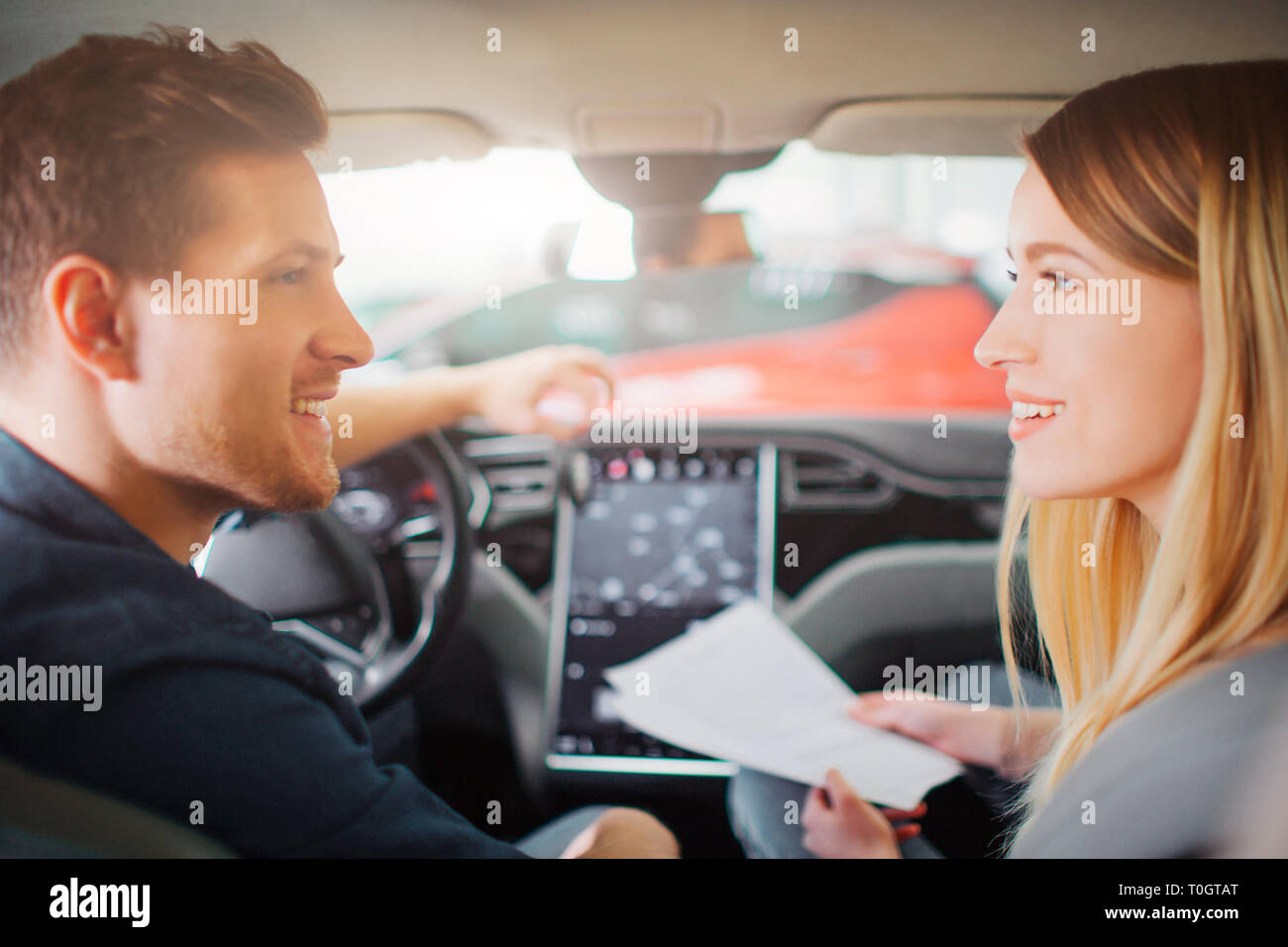 Young couple buying first electric car in the showroom. Attractive family talking about car purchase in the cabin of modern electric hybrid vehicle - Stock Image