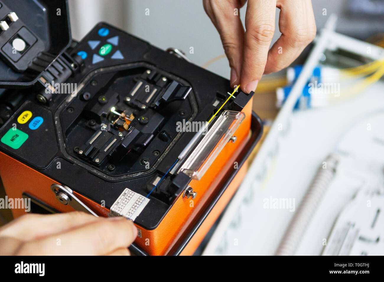 worker comunicate fiber optic cable at opto box. installing new network equipment. - Stock Image