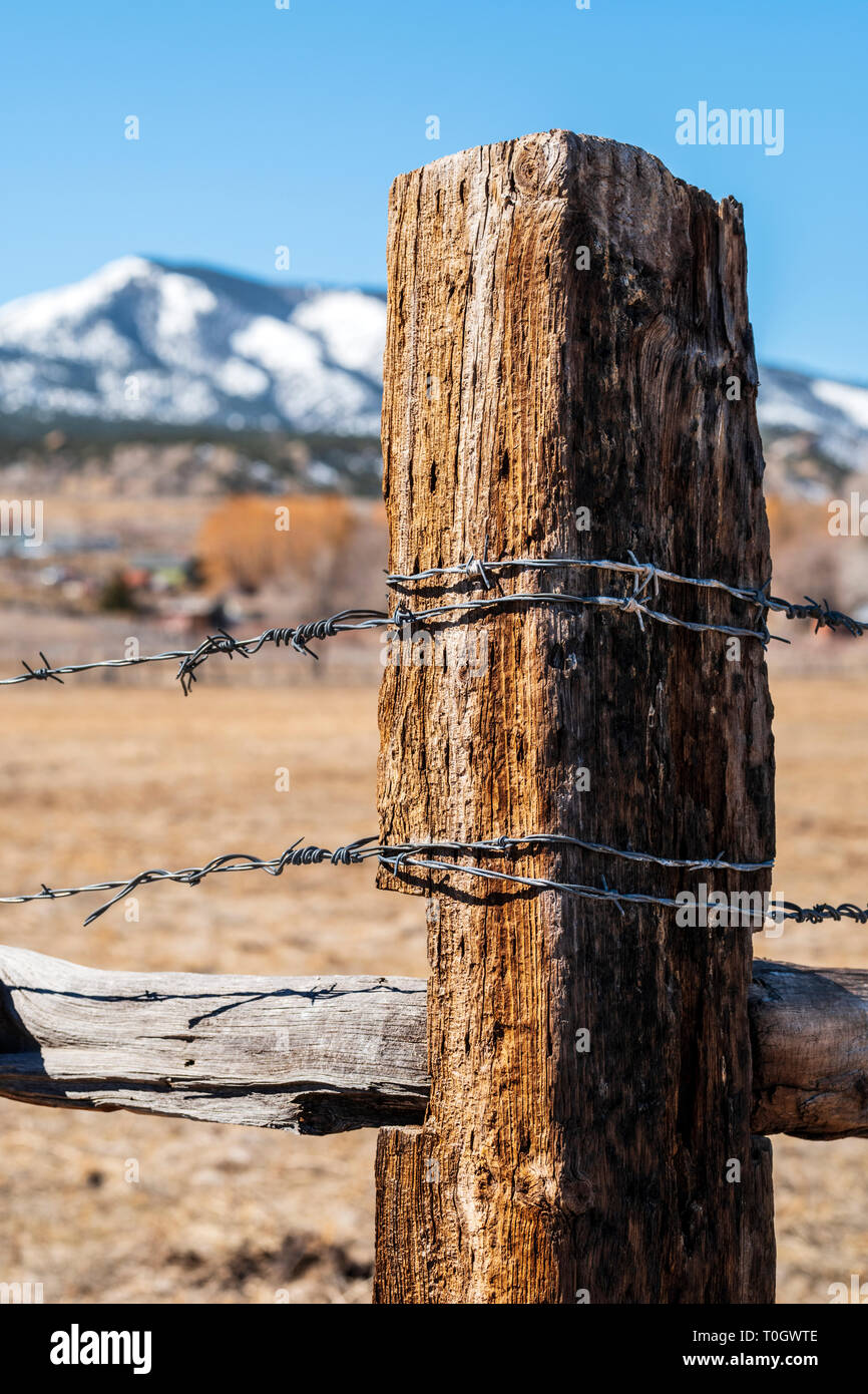 Close-up of barbed wire fence & wooden fence post; ranch in Central Colorado; USA - Stock Image