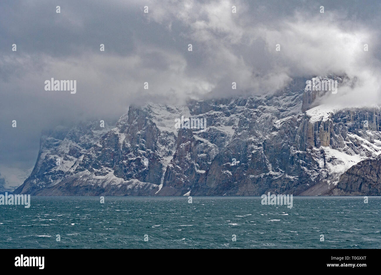 Stormy Clouds on Jagged Coastal Mountains along the Sam Ford Fjord on Baffin Island in Nunavut, Canada - Stock Image
