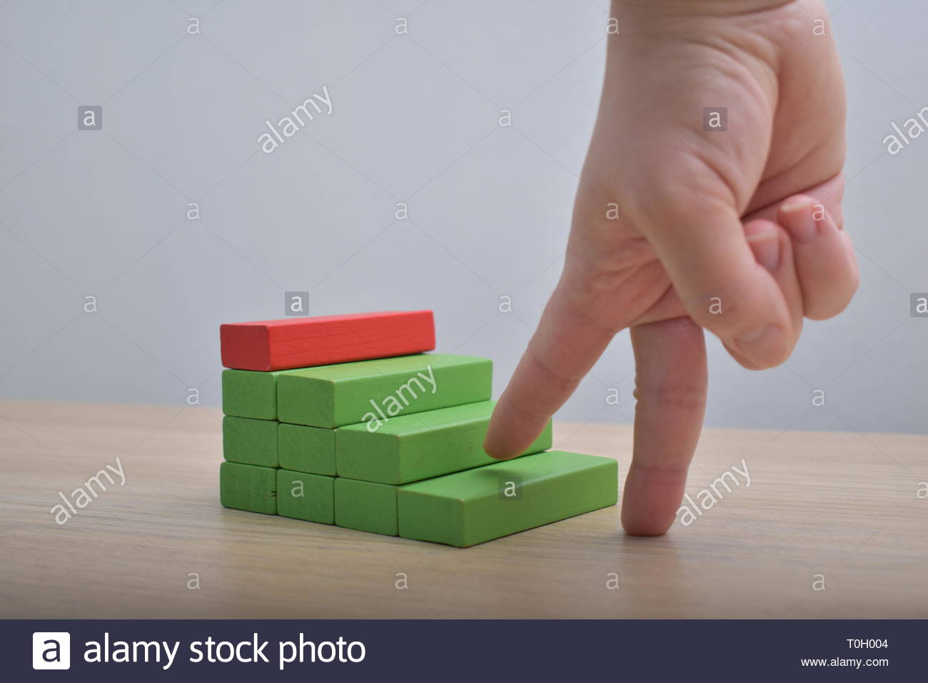 Giving the first step Wooden blocks ladder and fingers career path concept - Stock Image