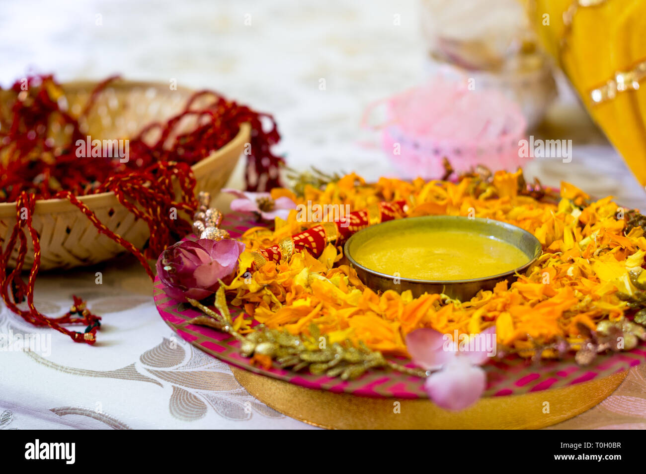 Traditional Haldi turmeric kept on a flower plate for the hindu marriage ceremony Stock Photo