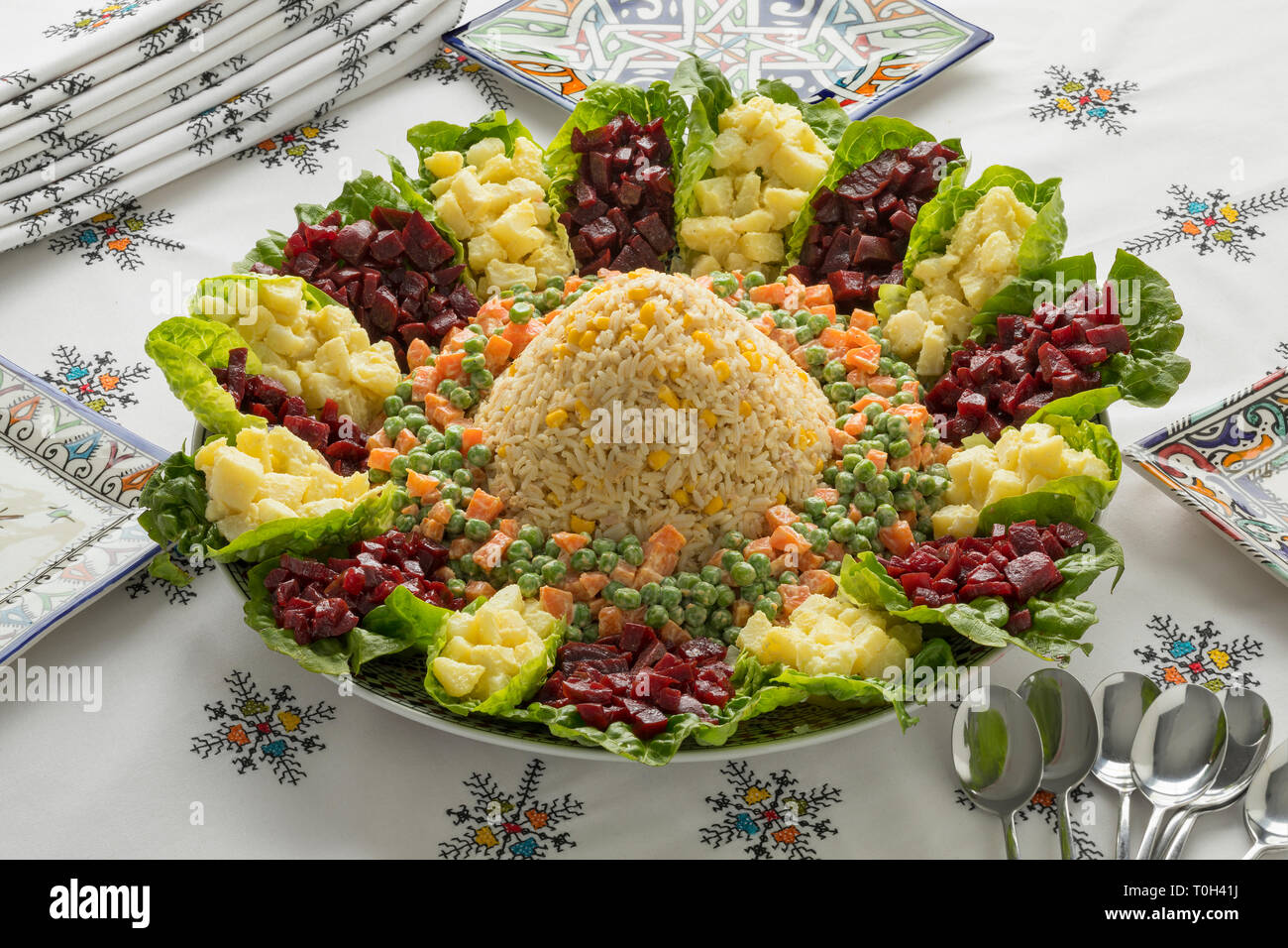 Dish with traditional festive Moroccan mixed salad on a nice set table with embroidered tablecloth - Stock Image