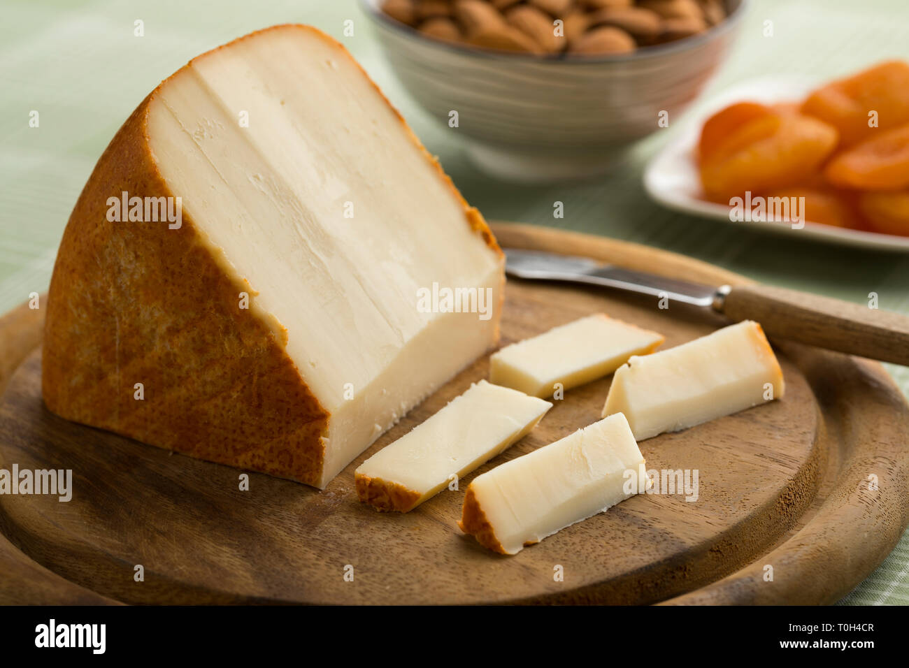 Piece of French sheep cheese and slices on a cutting board - Stock Image