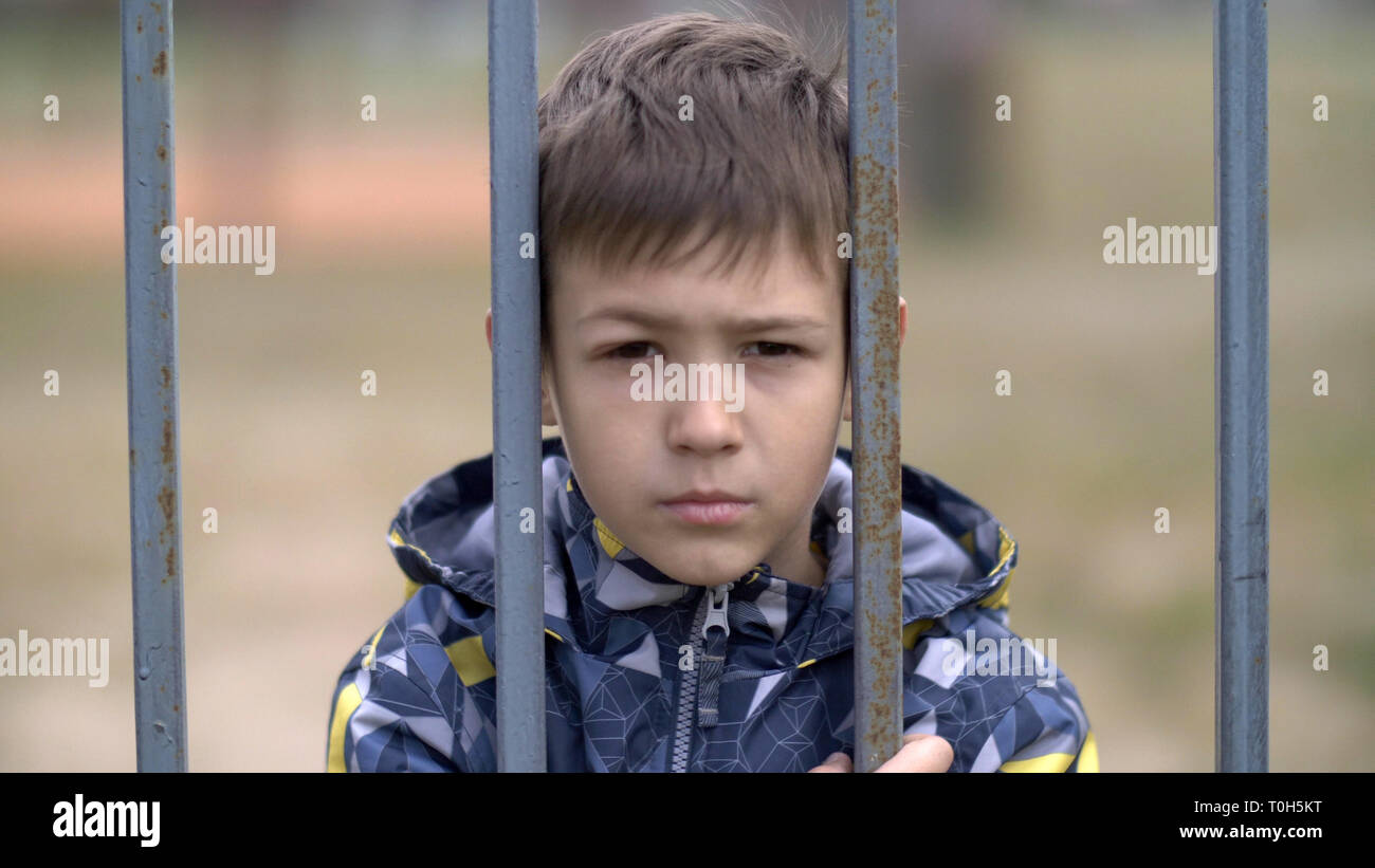angry boy behind an iron fence looks with hatred at the camera, bad boy with black eye - Stock Image