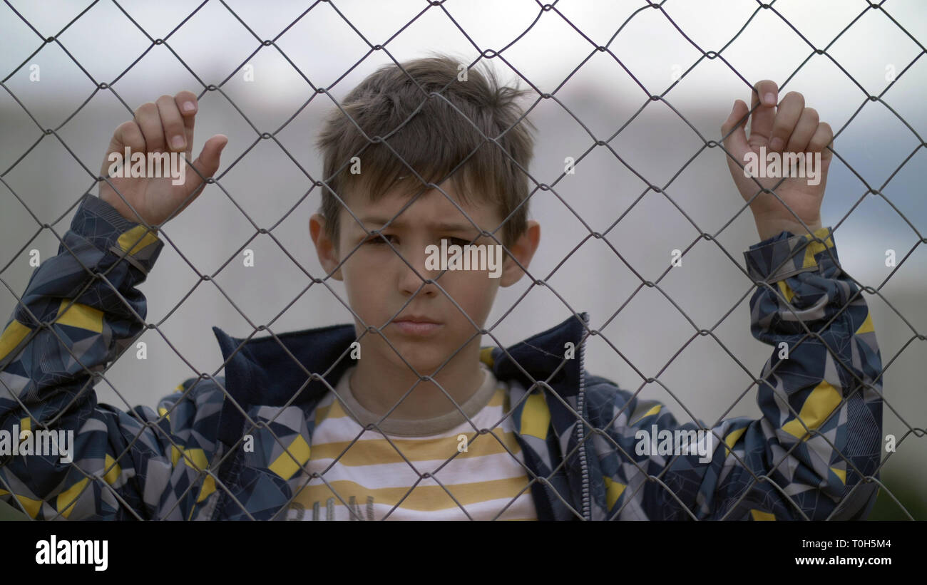 angry boy behind an iron fence looks with hatred at the camera, bad boy - Stock Image