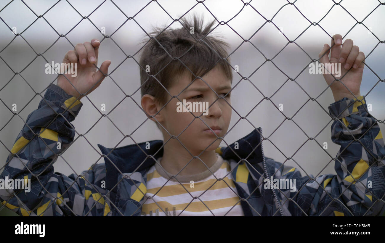 angry boy behind an iron fence looks with hatred, bad boy - Stock Image