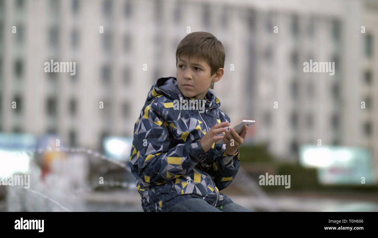 Frightened Boy Uses The Phone Carefully Looking Stock Photo