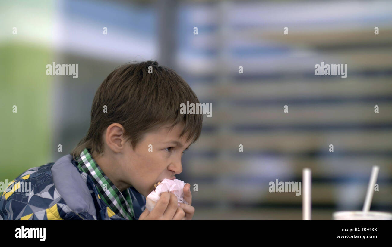 serious young teenager eating burger sitting in cafe in city - Stock Image