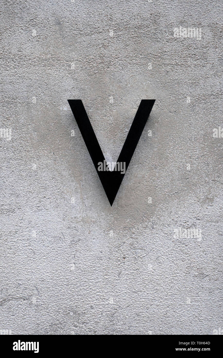 A Dark Metal Letter V Against A Stone Wall - Stock Image