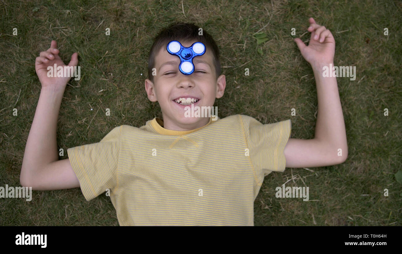 Happy boy twists the spinner on nose and lies on grass Outdoors - Stock Image