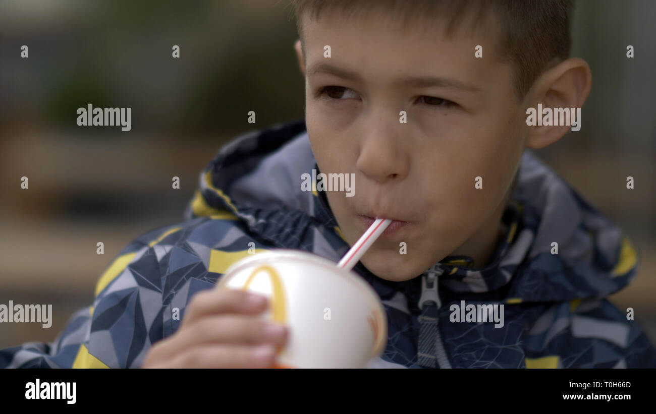 boy drinks a milkshake at a cafe outdoors - Stock Image