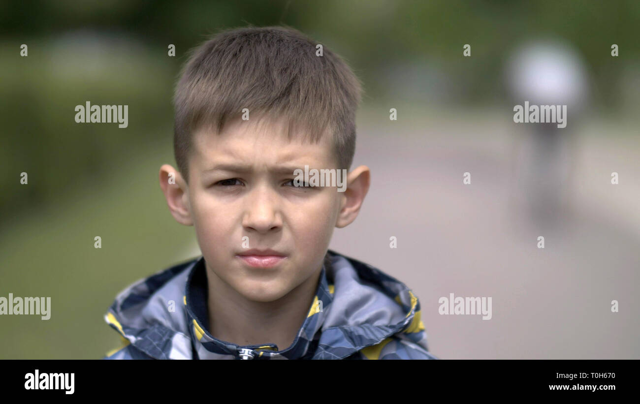 portrait of a serious boy with a tence glance looking at the camera, close-up heavy face - Stock Image