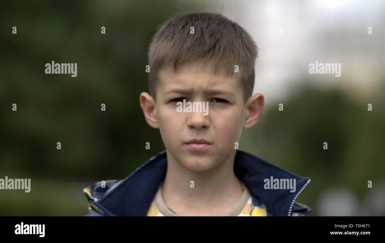 portrait of a serious boy with a tence glance looking at the camera, close-up heavy face Stock Photo