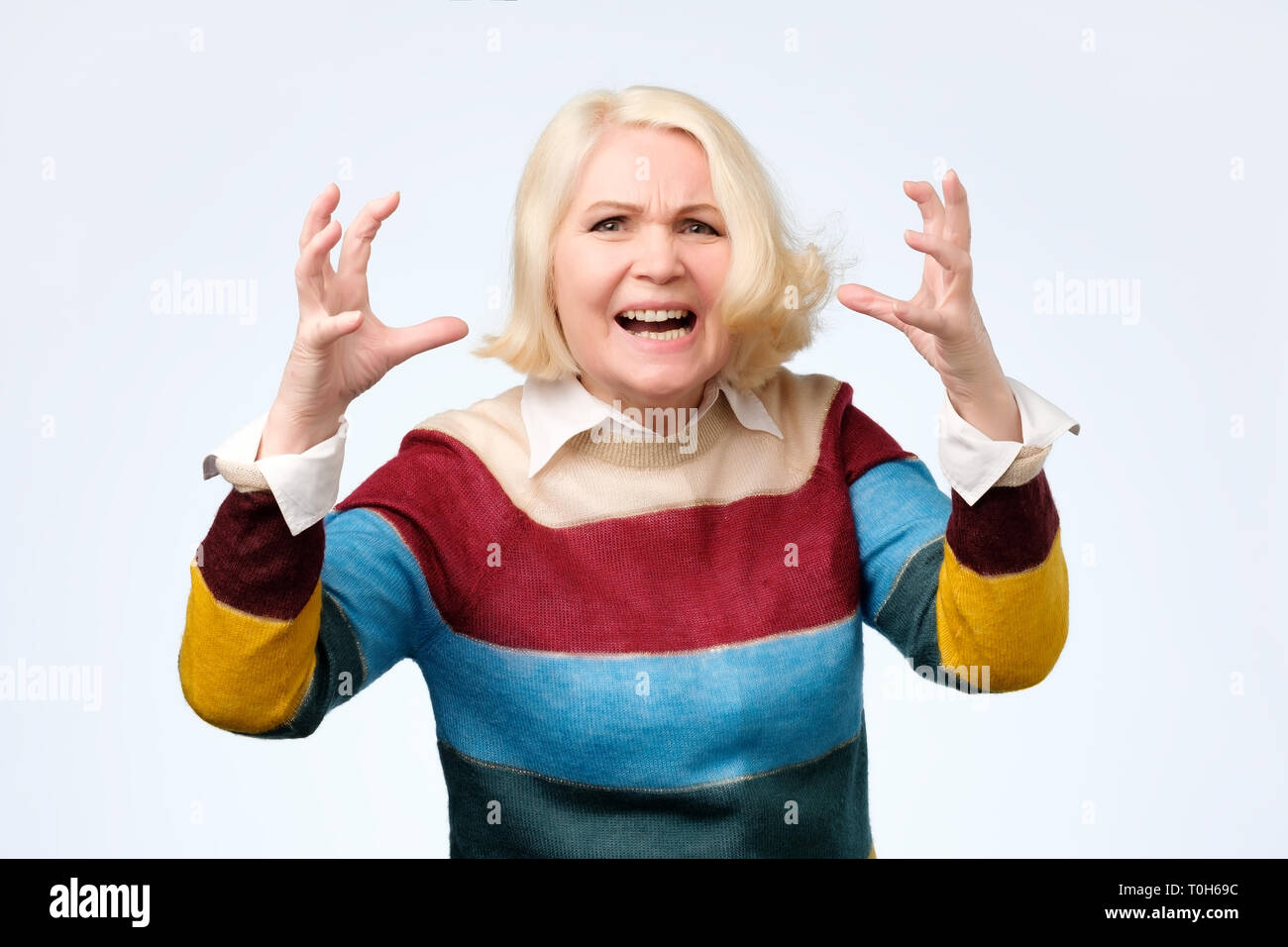 Angry old woman making angry facial gesture on white background - Stock Image