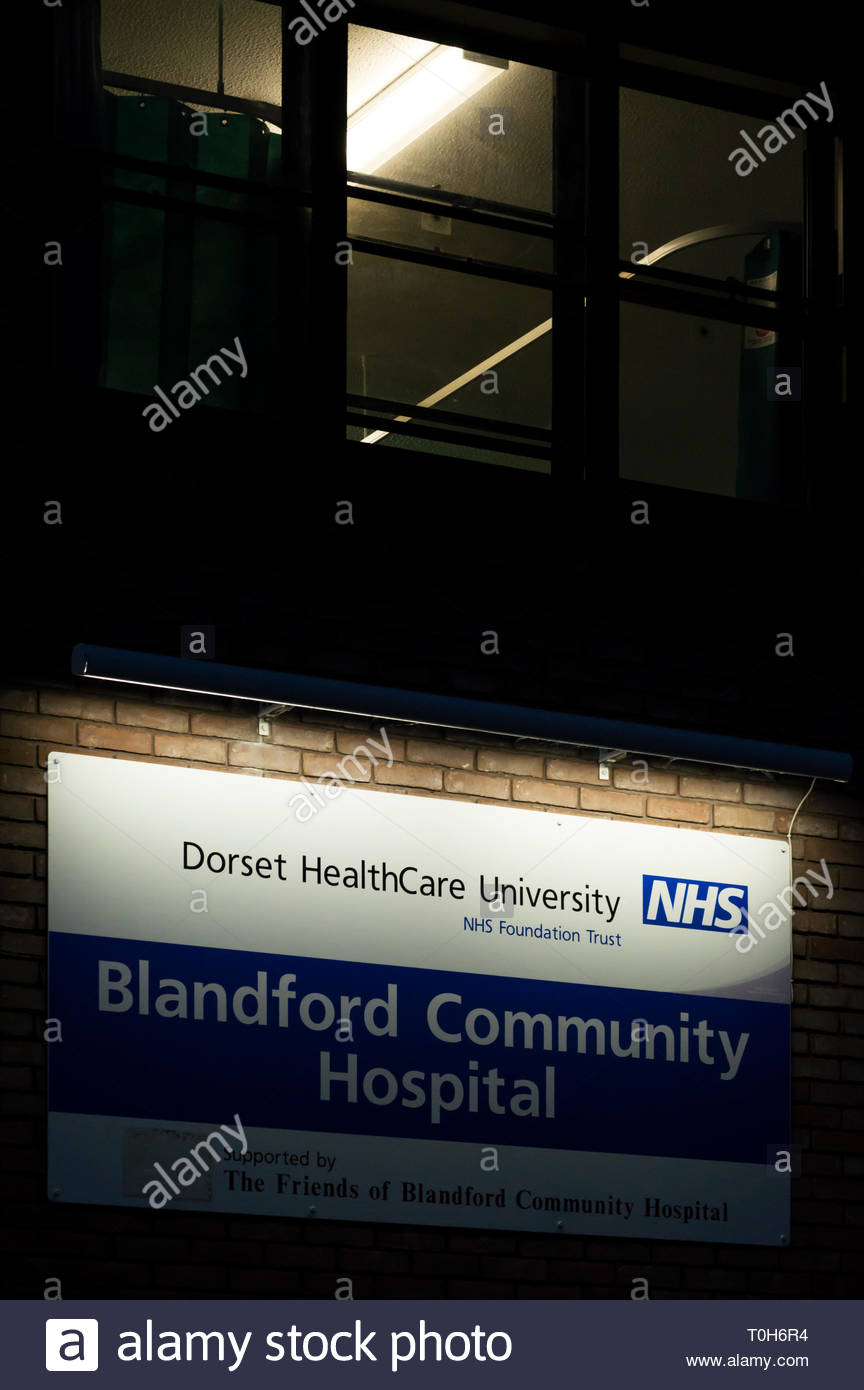 Close up nighttime image of a wall sign outside Blandford Forum Community Hospital, Dorset, England - Stock Image