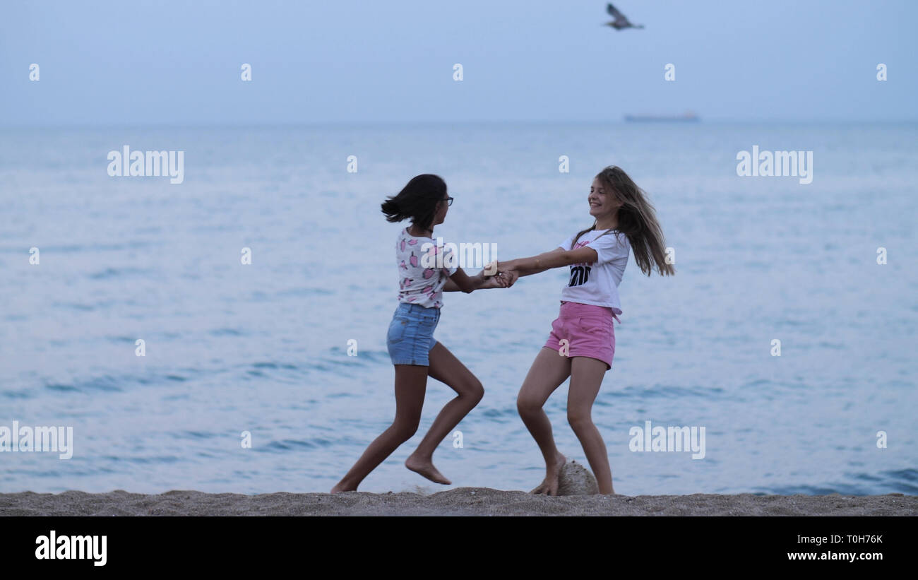 two happy girls whirling at the beach near the sea in the evening - Stock Image