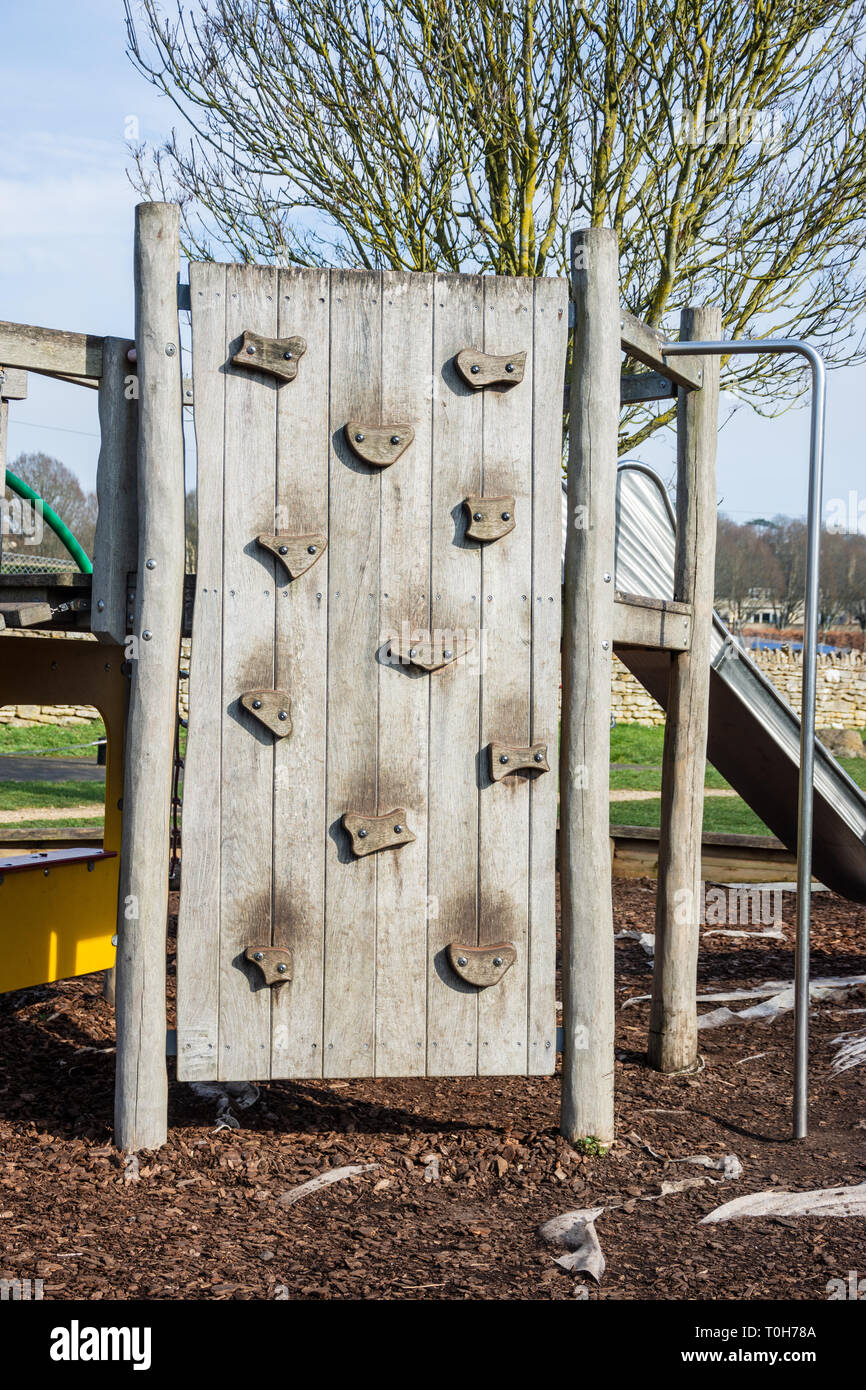 A childrens wooden climbing wall with large easy hand and footholds in a childs playground area Stock Photo