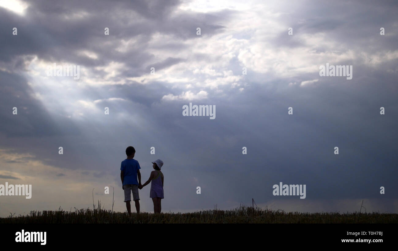 boy with girl walking on a background of beautiful clouds in the evening Stock Photo