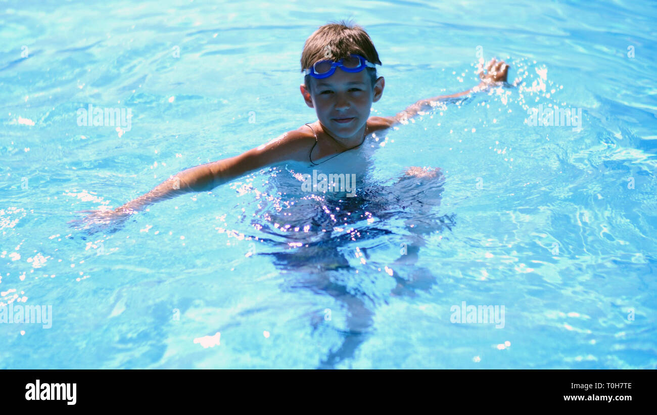 boy swimming goggles in the pool looking at the camera - Stock Image