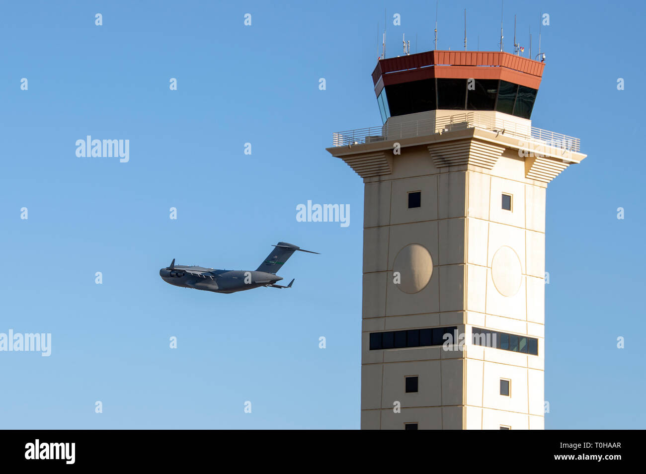 A U.S. Air Force C-17 Globe Master III assigned to McChord Air Force Base, Wash., flies past the control tower, Dec. 7, 2018 at Travis Air Force Base, Calif. The C-17 is capable of rapid strategic delivery of troops and all types of cargo to bases all over the world. The aircraft can perform tactical airlift and airdrop missions, as well as transport litters and ambulatory patients during aeromedical evacuations. (U.S. Air Force photo by Heide Couch) - Stock Image