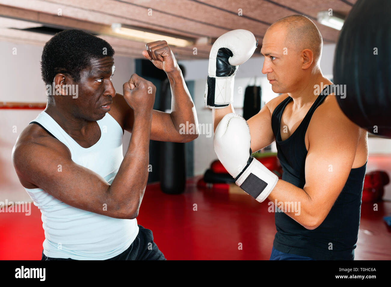 Glad cheerful positive african american trainer teaches man in boxing Stock Photo