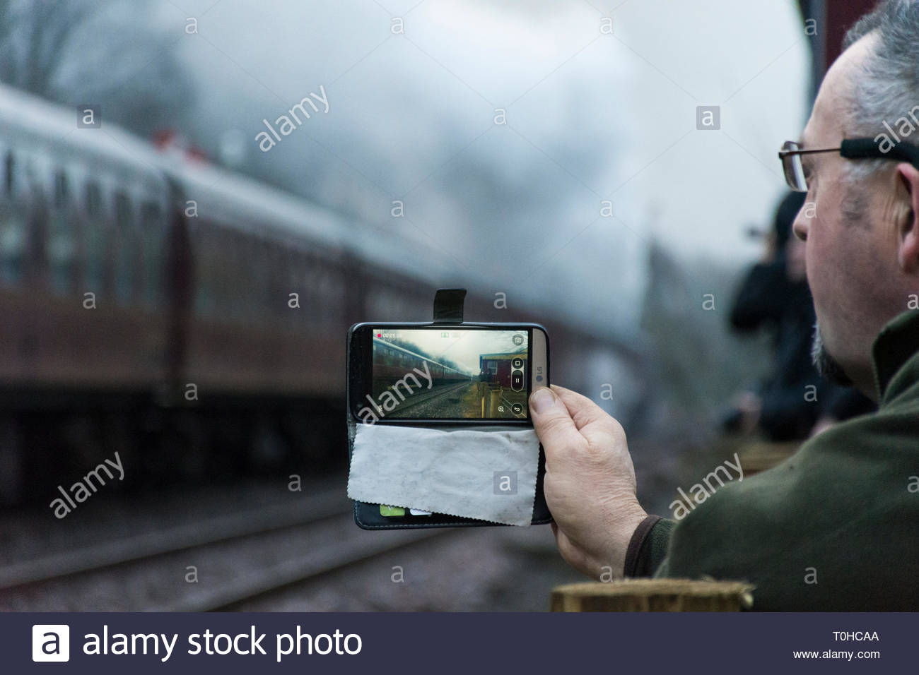 An enthusiast films the Bahamas steam locomotive on a smartphone as it leaves Appleby station on its journey south over the Settle to Carlisle line. - Stock Image