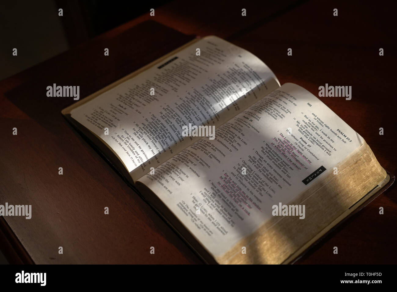Open bible on a dark wood table with light and focus on