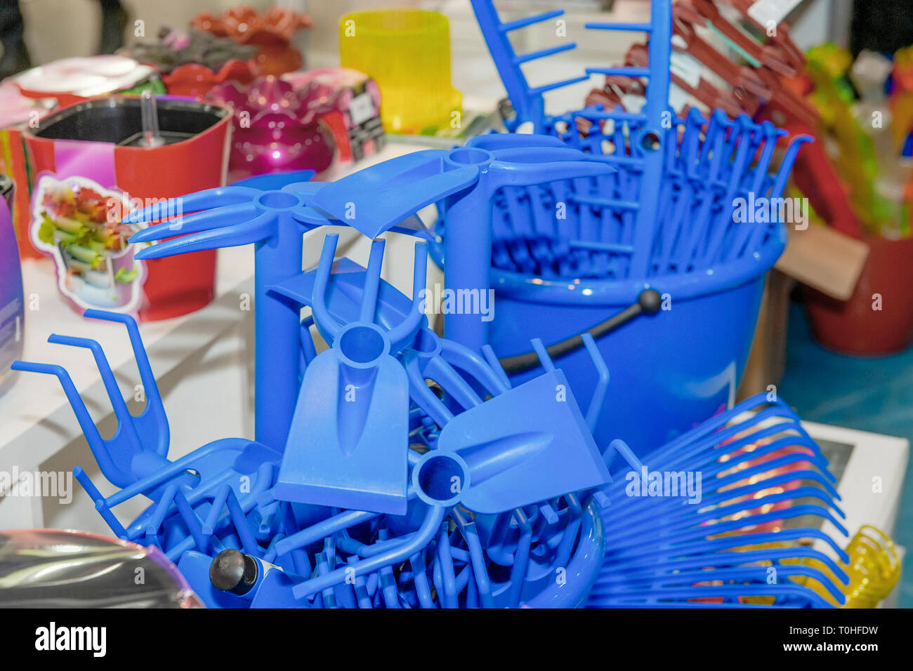 Blue rake Plastic products, plant care products in a supermarket display case. Recycled plastic. - Stock Image