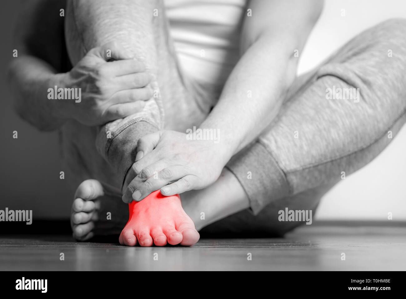 Causian man holds hands to his painful feet pain in foot black and white photography red color is area of pain