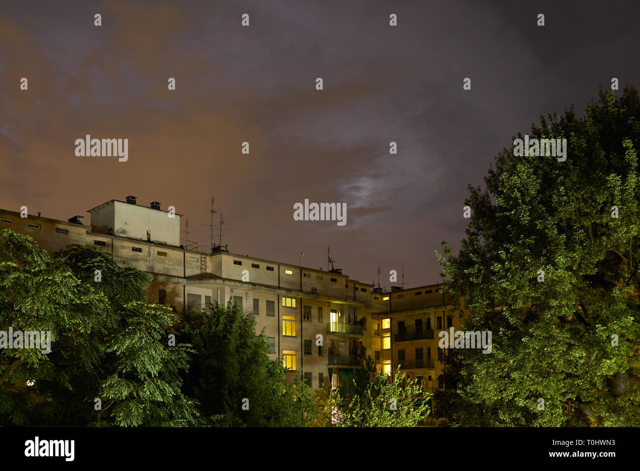 Buildings and green trees at night, illuminated sky in summer Stock Photo