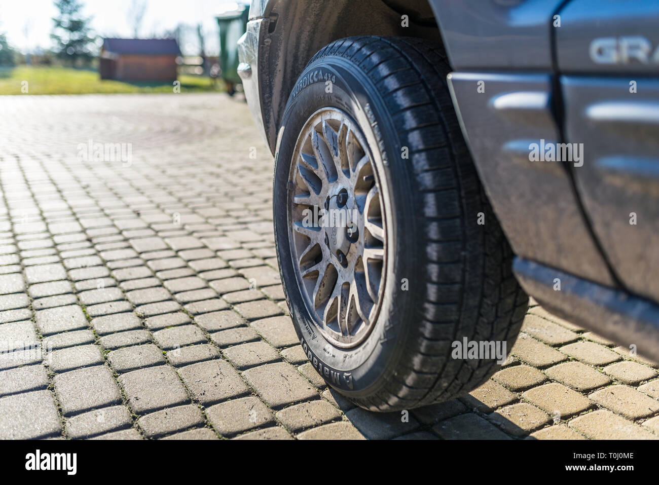 Torun, Poland - February 16, 2019. The view of the front, left wheel with aluminum rim, the Jeep Grand Cherokee WJ produced in 2002 with a diesel engi - Stock Image