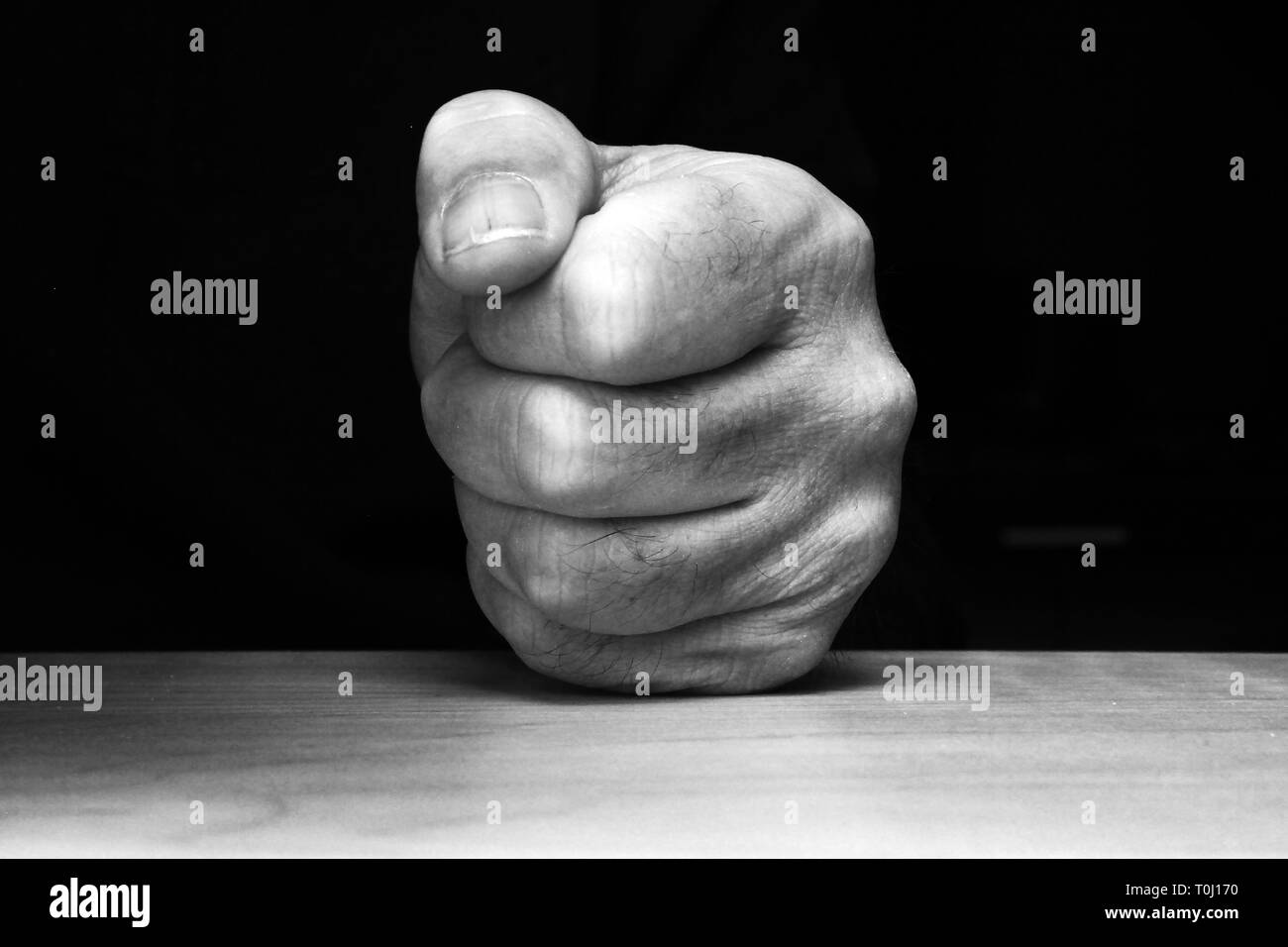 Fist pounding on a table - Stock Image