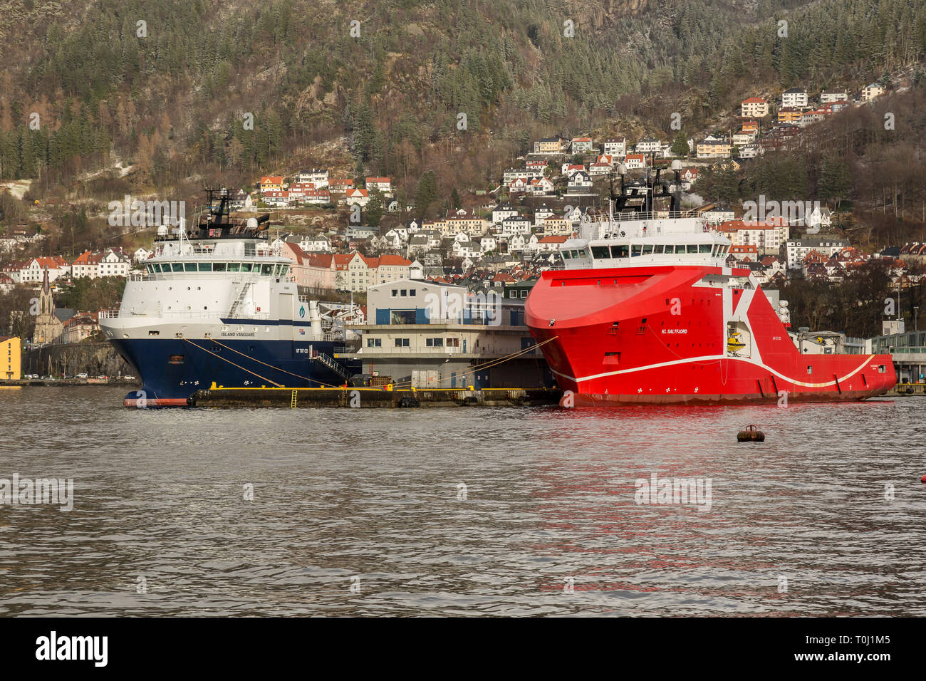 The Norwegian Off Shore Supply Ship KL Saltfjord and the Norwegian tug boat Island Vanguard, in the sea port of Bergen in Norway. - Stock Image