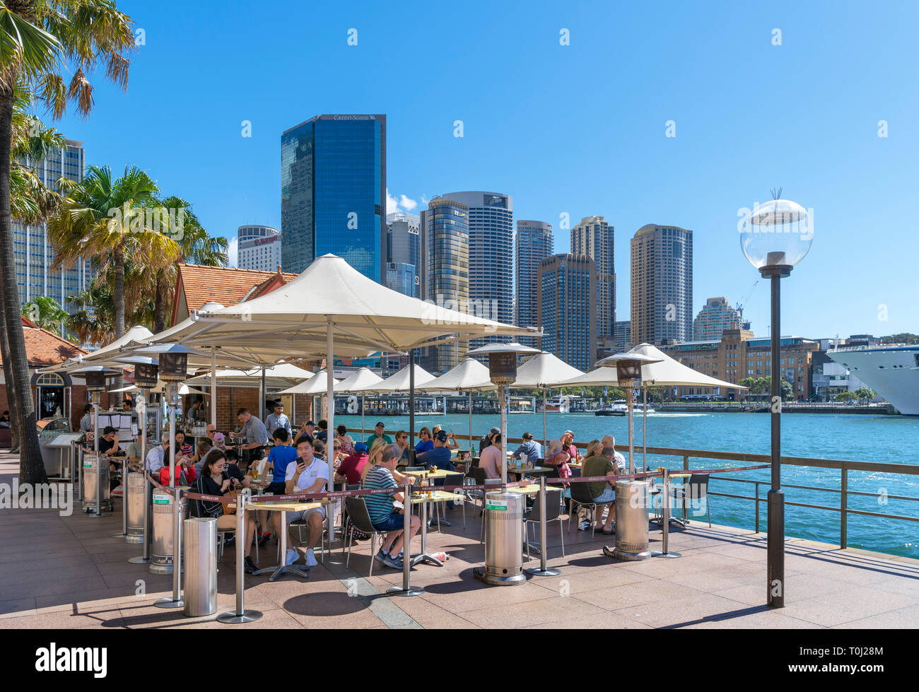 Sidewalk cafe on Circular Quay with the skyline of Sydney Central Business District behind, Sydney, Australia - Stock Image