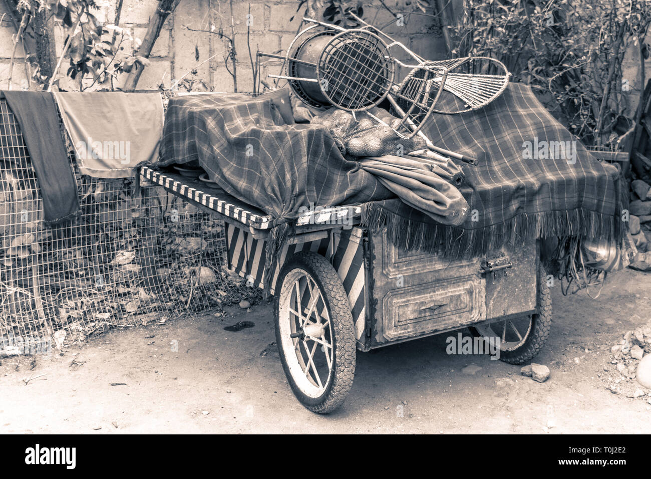 Old sales cart. Piled up with disused objects - Stock Image