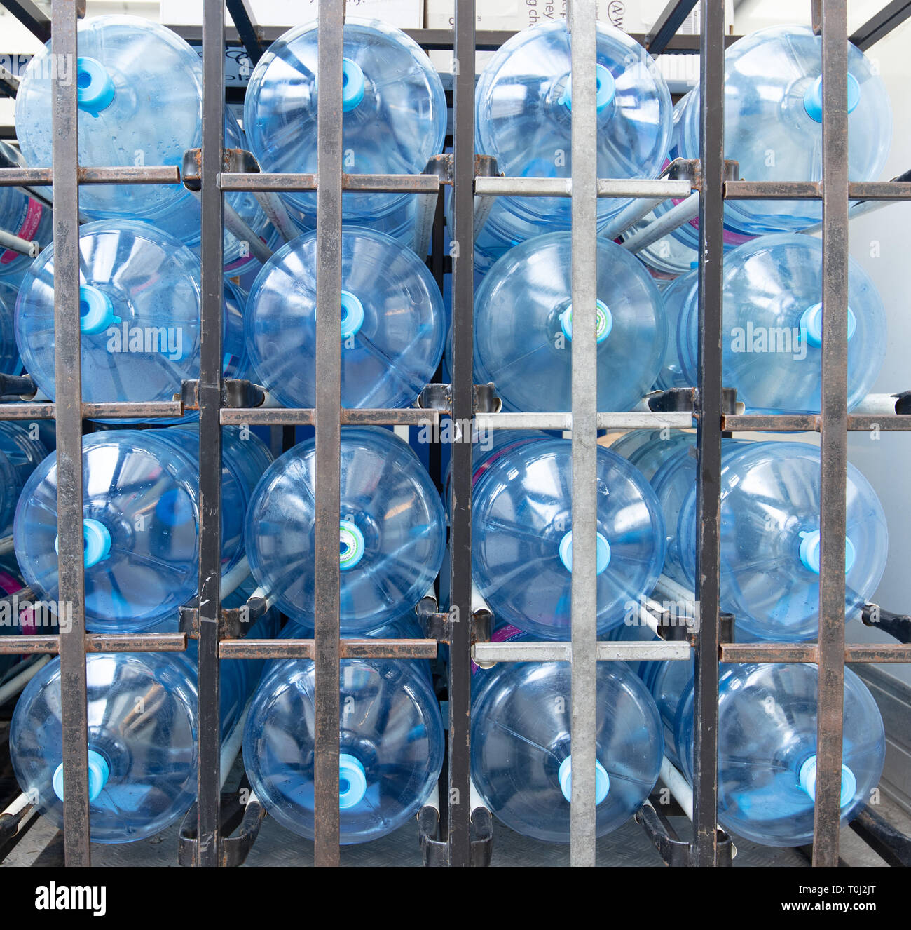 Group of large plastic water bottles neatly stacked in a frame inside a van for delivery to offices and other customers in central London, UK. - Stock Image