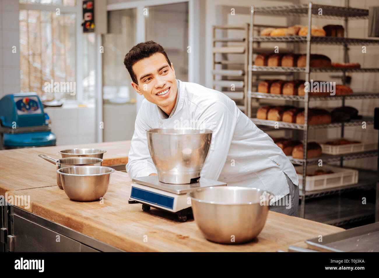 Baker standing in the modern kitchen near kitchen scale - Stock Image
