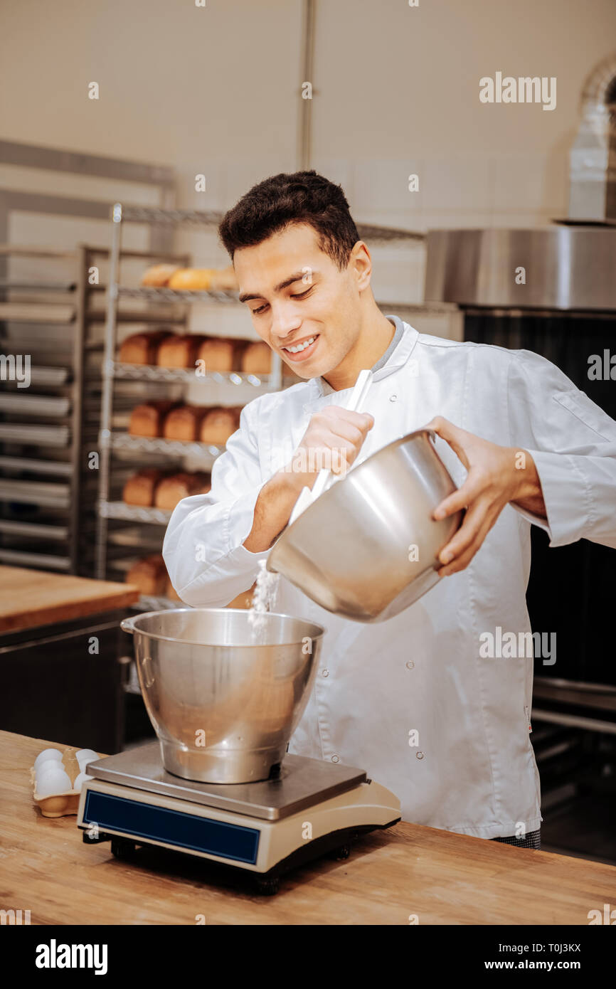 Young baker standing near kitchen scale and adding flour - Stock Image