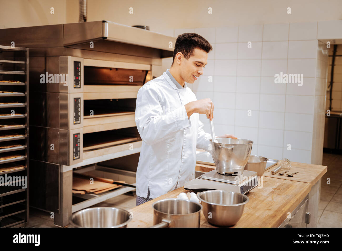 Baker standing near big professional oven and kitchen scale - Stock Image