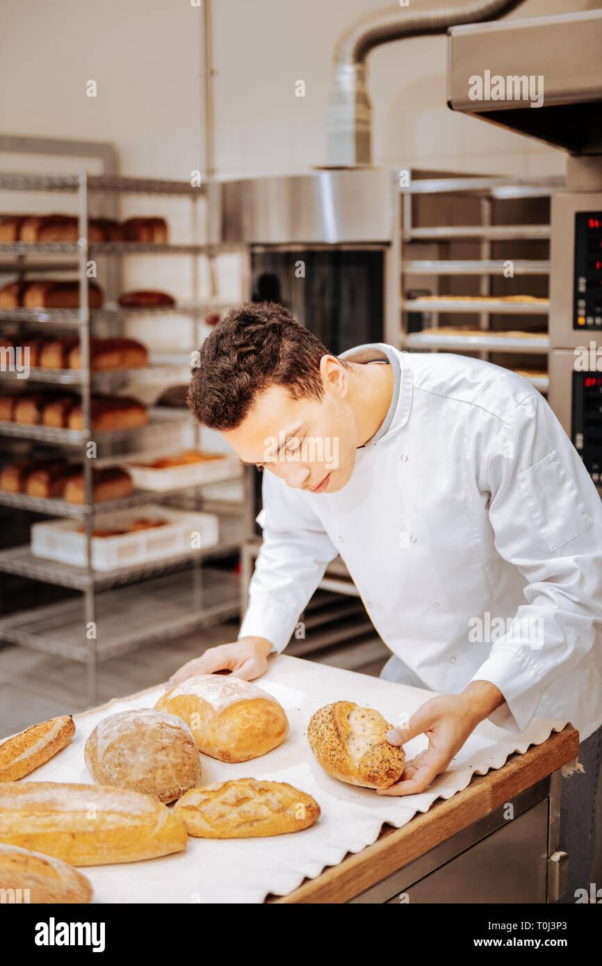 Baker looking at the tray and checking the readiness of bread - Stock Image
