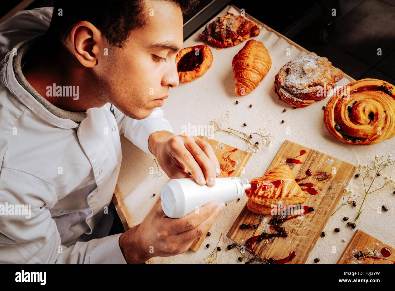 Diligent young baker feeling joyful while decorating pastry Stock Photo