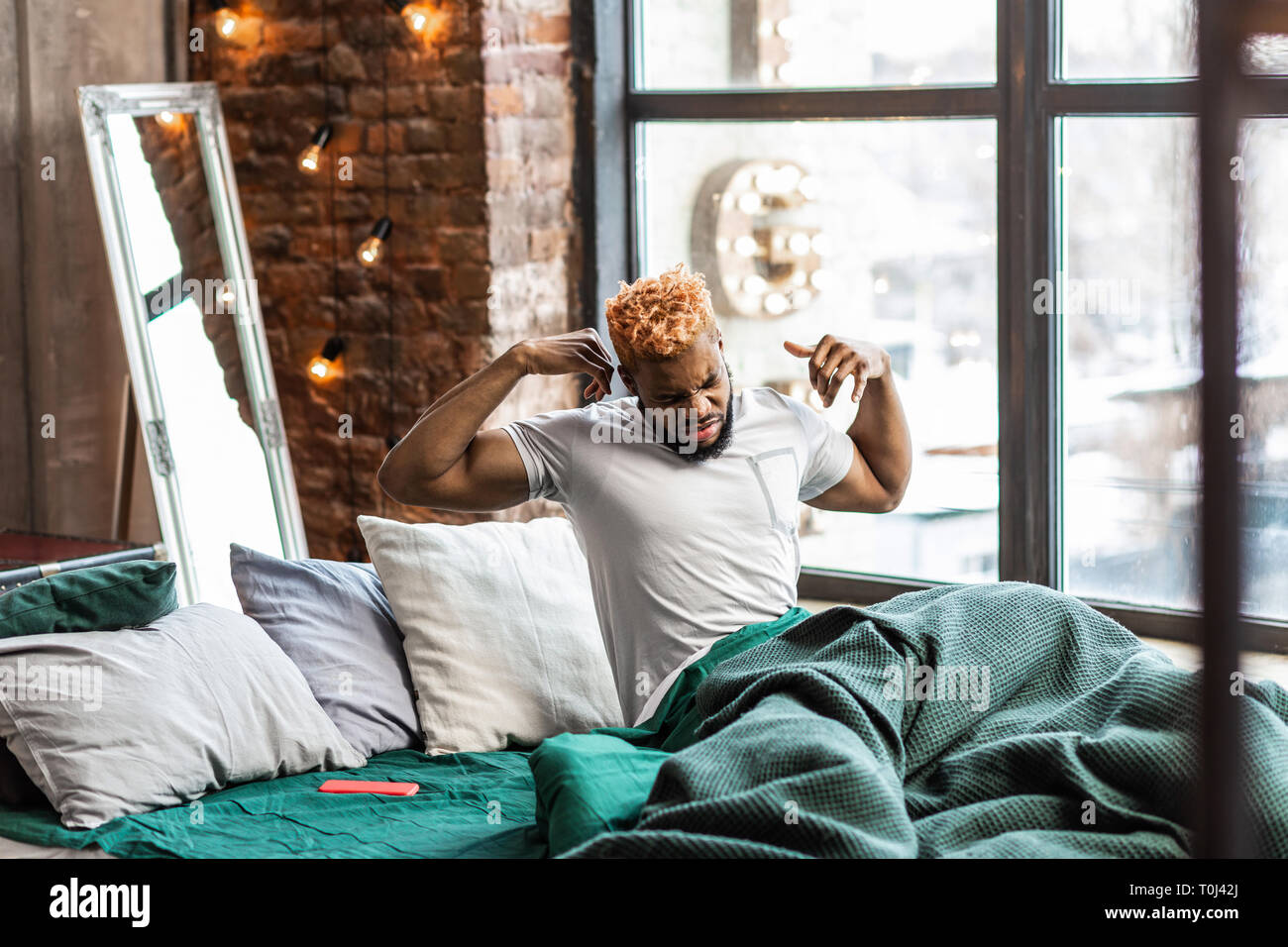 Nice sleepy man getting up in the morning - Stock Image