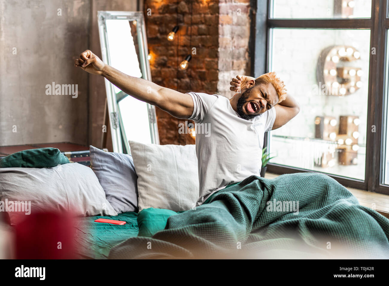 Pleasant Afro American man waking up in his bed - Stock Image