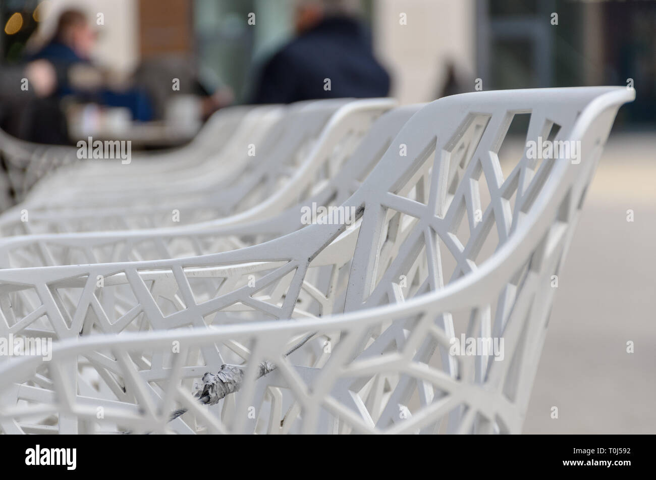 Row Of White Plastic Patio Chairs In Close Up With Selective