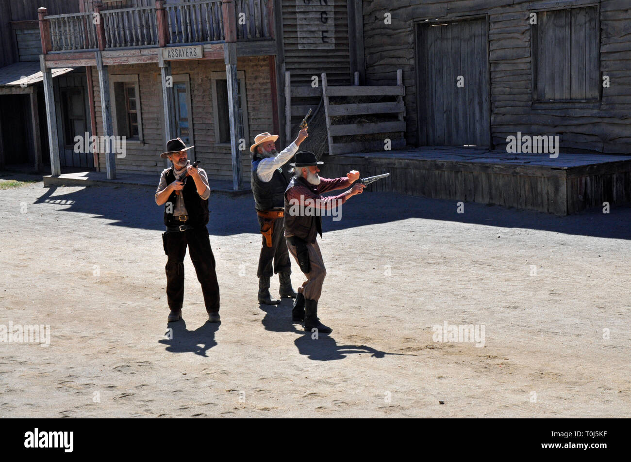 Cowboy actors re-enact a gunfight scene for tourists on a former Western film set in Tabernas, Almeria, Spain. - Stock Image