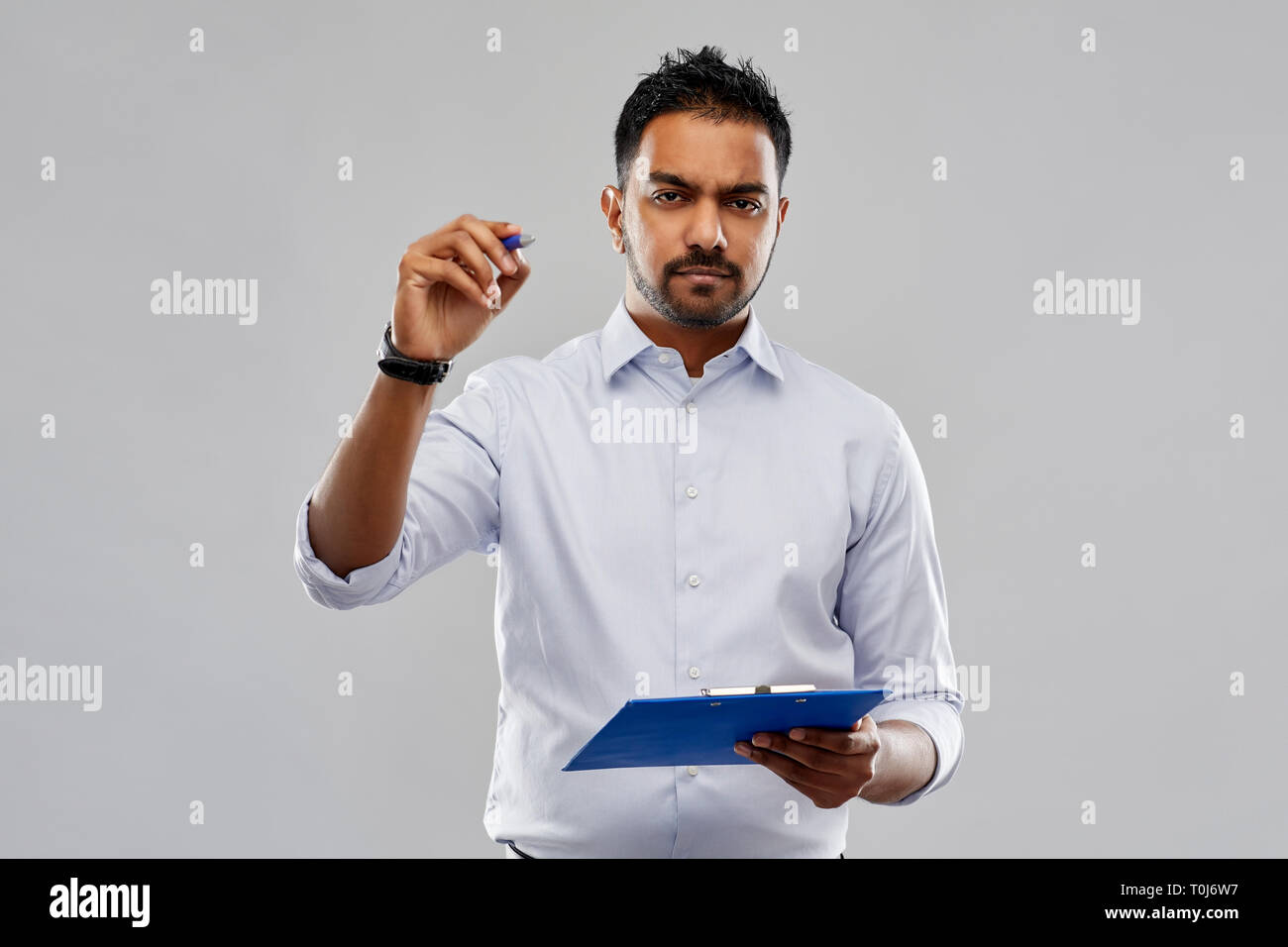 strained indian businessman writing to clipboard - Stock Image
