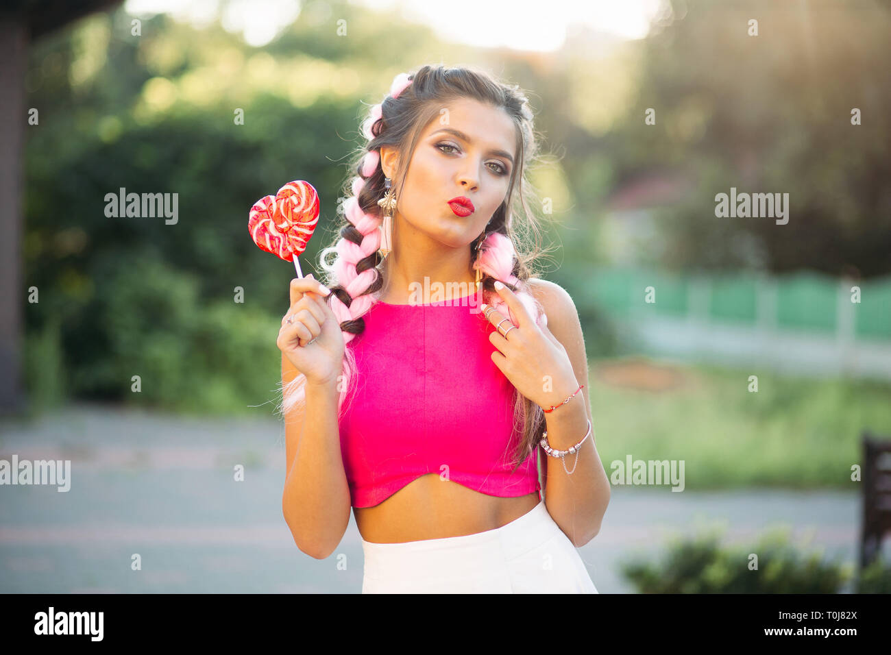 Pretty and positive girl in pink top holding candy heart on stick. Stock Photo
