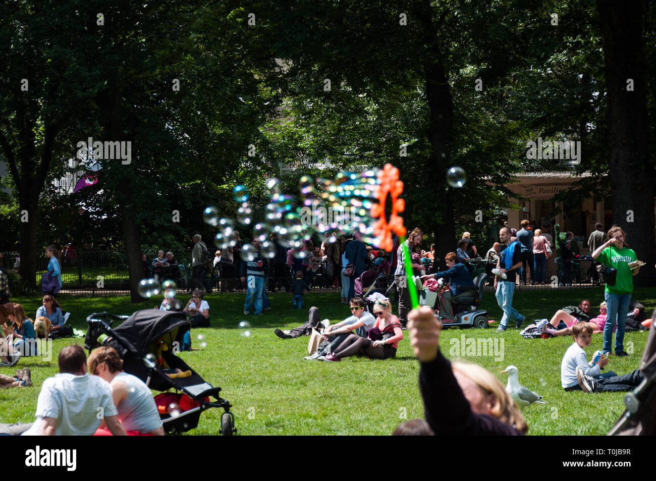 People sitting in park enjoying day out on warm sunny summer day at the Royal Pavilion Gardens in Brighton UK - Stock Image